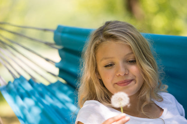 Woman looking at dandelion seed head in Aqua blue Florida hammock