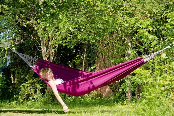 Woman lying with arm hanging in Berry purple Florida hammock