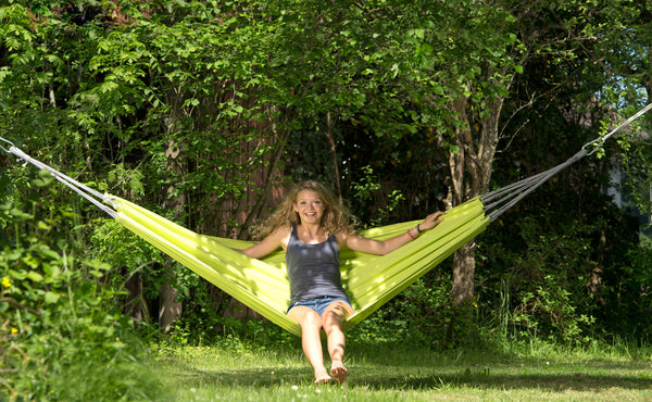 Girl sitting and swinging in Kiwi green Florida hammock