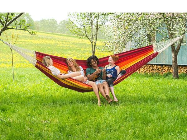 Four people in red orange striped Gigante Lava hammock