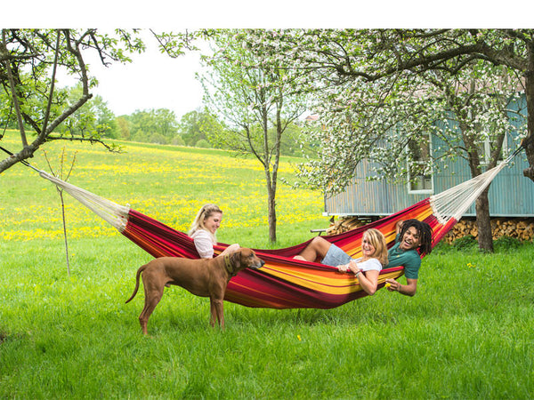 Three people with a dog relaxing in red orange striped Gigante Lava hammock