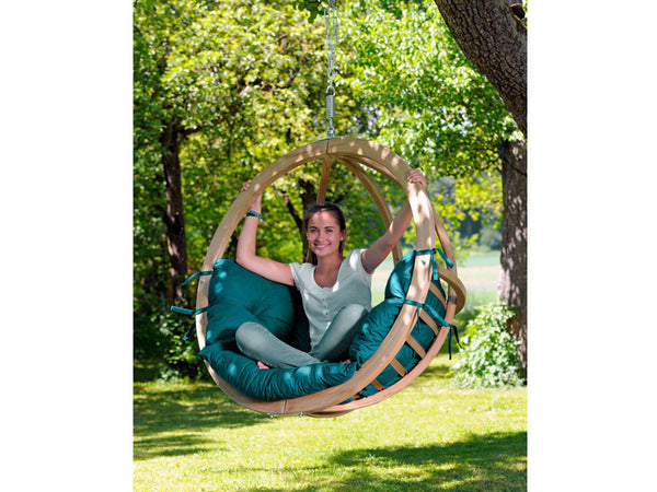 Girl sat in Globo Single Green Wooden Swing Chair hanging from tree.