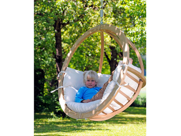 Child sat in Globo Single Natura Wooden Swing Chair hanging from tree.