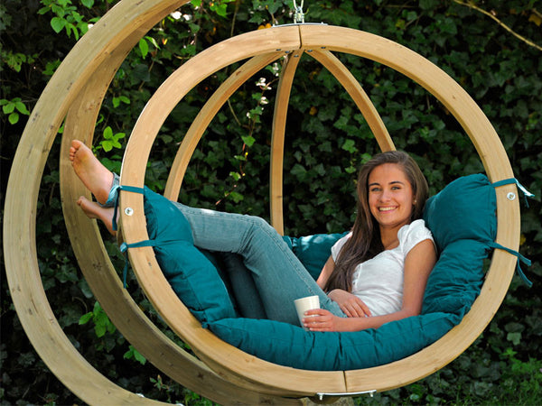 Close up of woman sat in Globo Single Green Wooden Swing Chair Set