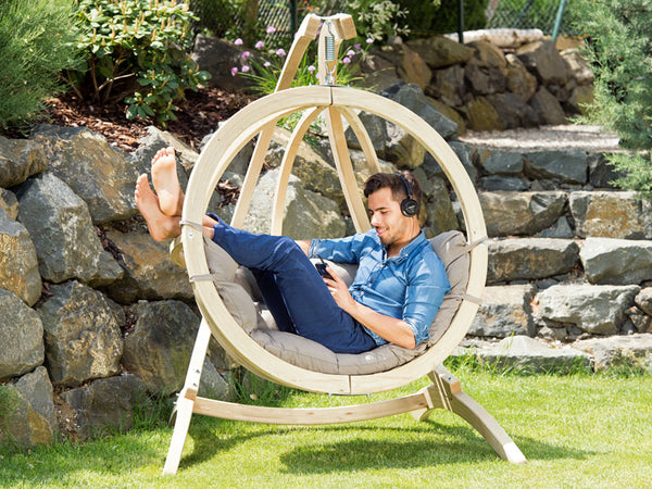 Man lying in Globo Single Taupe Wooden Swing Chair Set