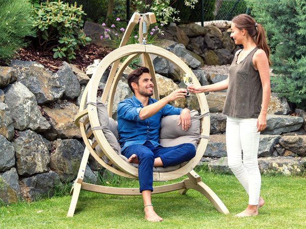 Man receiving drink sat in Globo Single Taupe Wooden Swing Chair Set