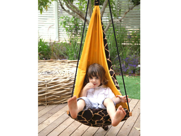 Child sat in giraffe patterned hanging chair.