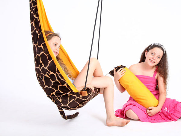 Child sat in giraffe patterned hanging chair with another young girl watching.