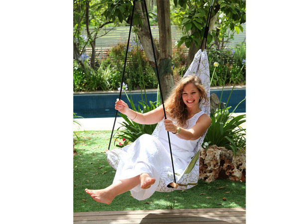Woman sat in Peppermint Hang Solo Hammock Chair on decking.