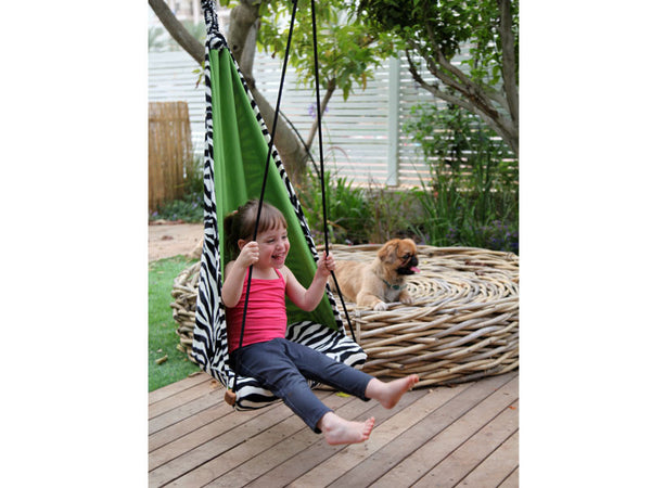 Child sat in zebra patterned hanging chair.
