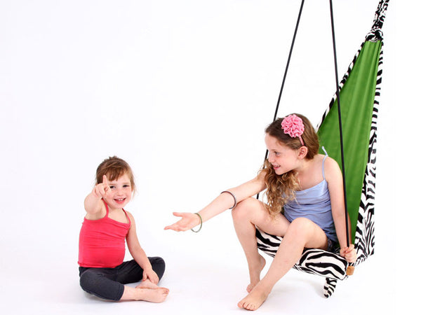 Girl with younger child sat in zebra patterned hanging chair.
