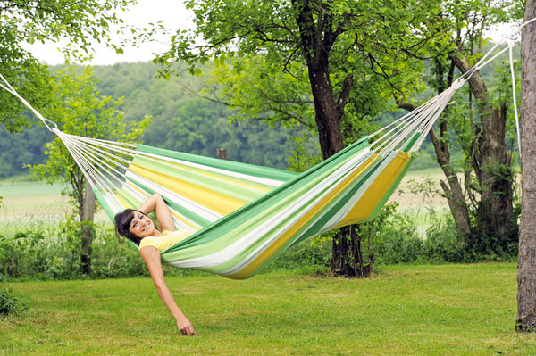 Girl lying with hanging arm in striped green yellow white striped Apple Lambada hammock