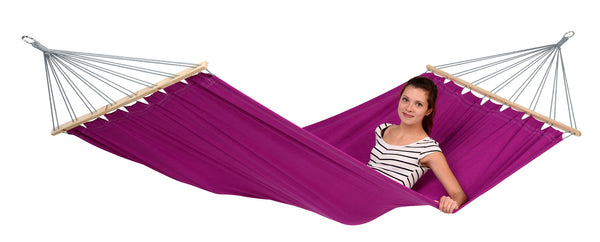 Woman lying on Berry purple Miami hammock with white background.