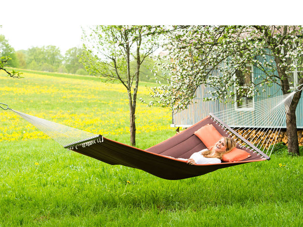 Woman lying on terracotta Palm Beach hammock in front of shepherds hut.
