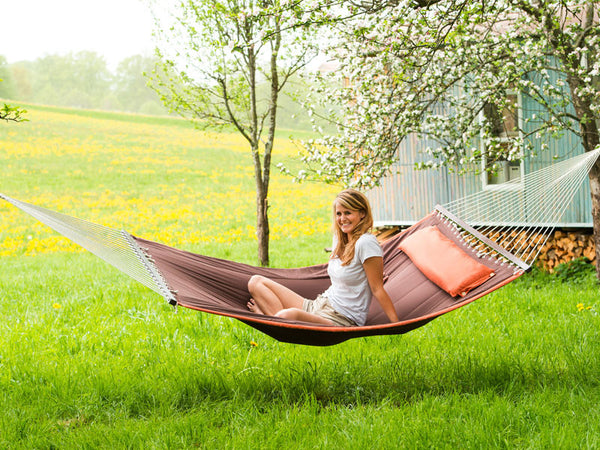 Woman sitting on terracotta Palm Beach hammock in front of shepherds hut.
