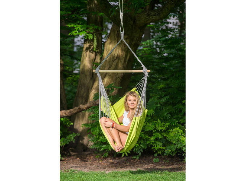 Girl sat under large tree in kiwi Panama hammock chair.