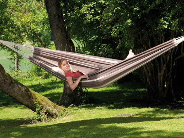 Woman lying in cafe Paradiso hammock in garden.