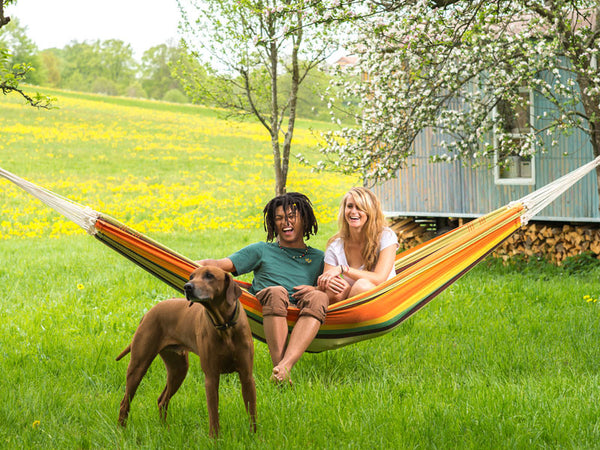 Couple with dog sat in esmerelda Paradiso hammock.