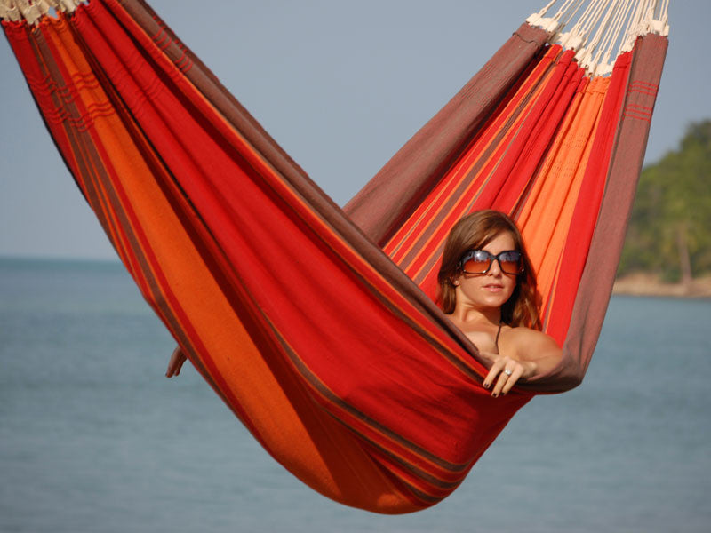 Woman lying in terracotta Paradiso hammock by the sea.