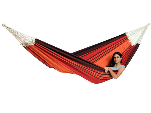 Woman lying in terracotta Paradiso hammock with white background.