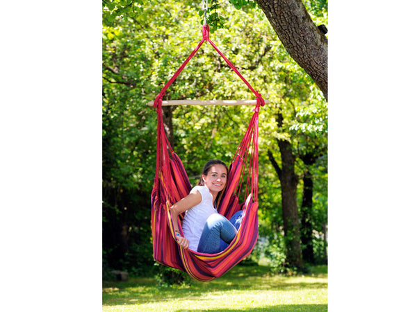 Girl sat in vulcano Relax hanging chair in garden.