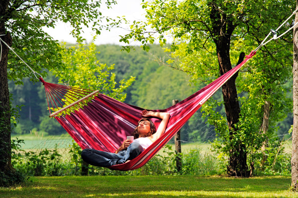 Girl lying crossed legs with mobile in purple stripes Samba Fuego hammock with spreader bar