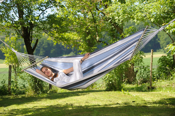 Girl lying in blues and white striped Samba Marine hammock with spreader bar