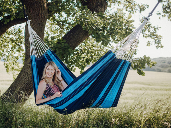 Woman lying in striped Blue Santana hammock under tree