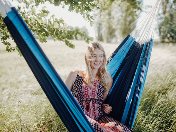 Woman sat in striped Blue Santana hammock under tree