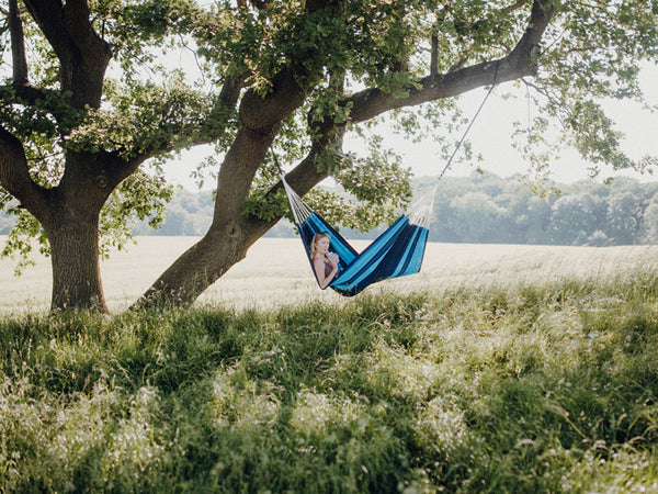 Woman lying in striped Blue Santana hammock under tree in distance