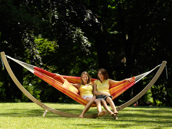 Two girls sitting in orange papaya striped Barbados hammock with stand set