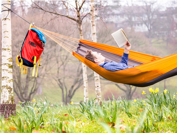 Man reading in Silk Traveller Hammock Techno Orange Grey.