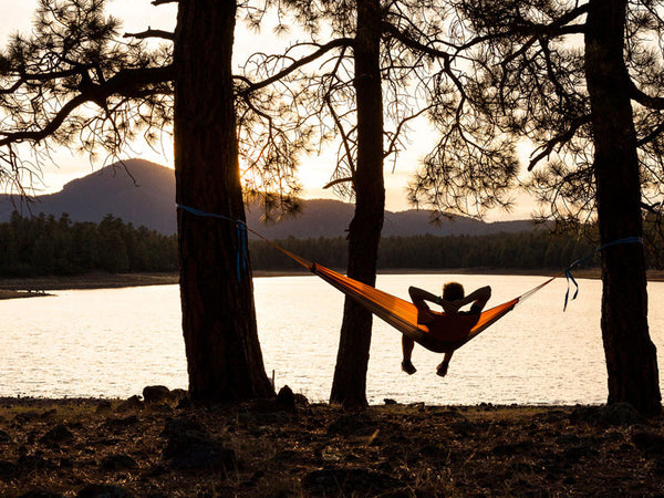 Man sitting in Silk Traveller Hammock Techno Orange Grey overlooking lake