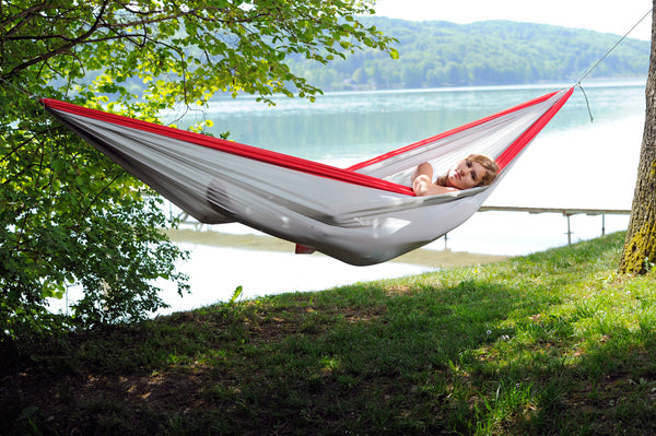 Woman lying in Silk Traveller XXL Hammock by lake