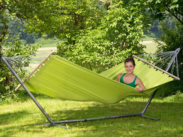 Woman sitting up in hammock supported by Sumo Rockstone Hammock Stand.
