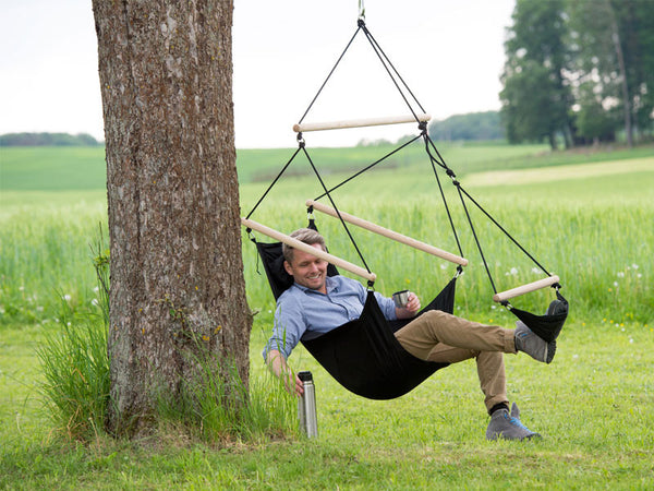 Man sitting in black Swinger Hammock Chair.