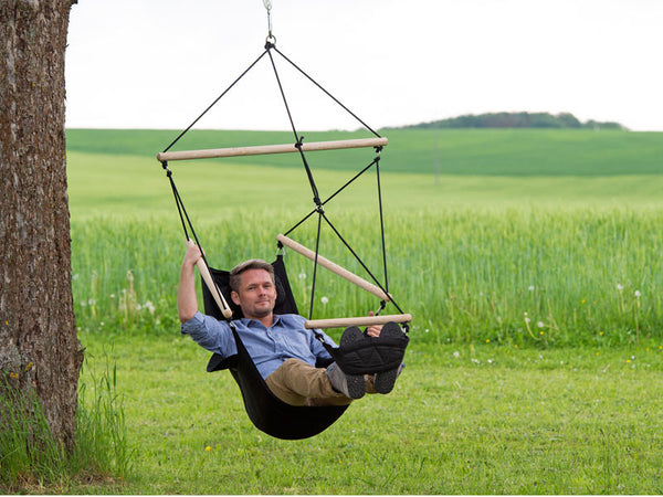 Man swinging in black Swinger Hammock Chair.