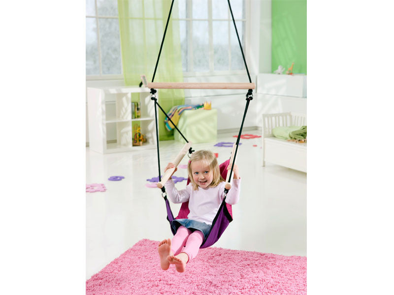 Young girl swinging in Kid's Swinger Pink Child's Hanging Chair indoors.