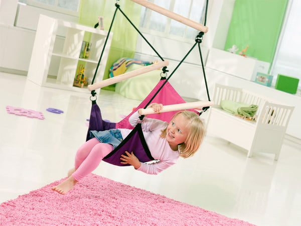 Young girl sat in Kid's Swinger Green Child's Hanging Chair indoors.