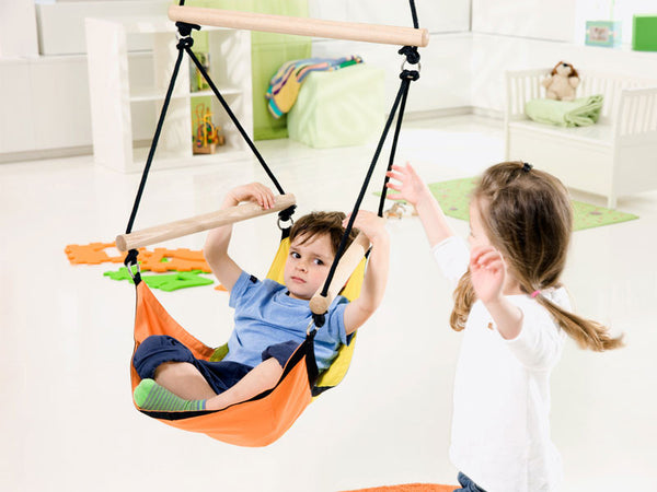 Boy swinging in Kid's Swinger Yellow Child's Hanging Chair indoors.