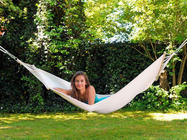 Girl lying on front in white Tobago hammock with spreader bar