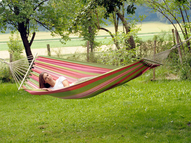 Girl lying in pinks and greens striped Tonga Bubblegum hammock with spreader bar