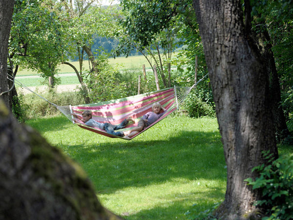 Two children lying in pinks and greens striped Tonga Bubblegum hammock with spreader bar