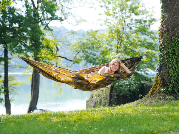 Woman lying in camouflage Travel Set hammock.
