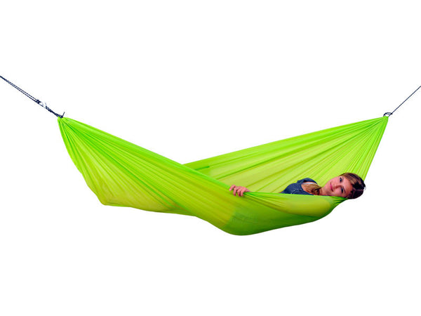 Woman lying in lime Travel Set hammock with white background.