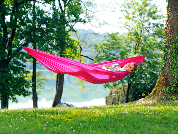 Woman lying in pink Travel Set hammock.