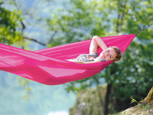 Close up of woman lying in pink Travel Set hammock.