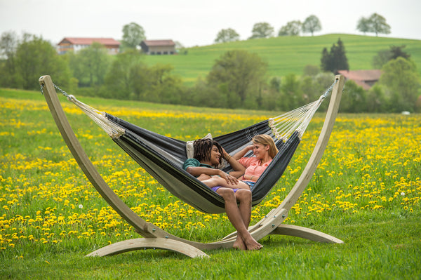 Couple sat in hammock supported by Troja Hammock Stand