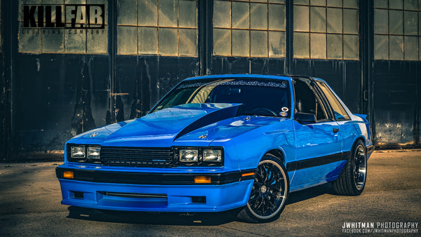 Johnny Detamore built his 1985 Mustang into his coupri, a capri bumper, fenders and rear quarters, Xenon air dam, sn95 interior, custom wheels, IRS rear, blown 2v stroker using a procharger, added t-tops and painted it grabber blue.
