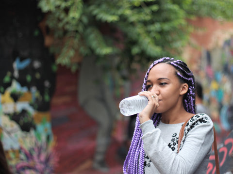 Black woman with protective style braids drinking water